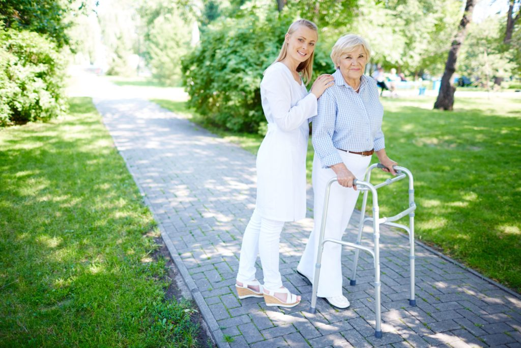 Pretty personal care nurse walking out with senior patient